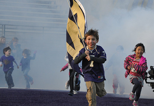 haring center children emerging through fog from tunnel at uw husky stadium