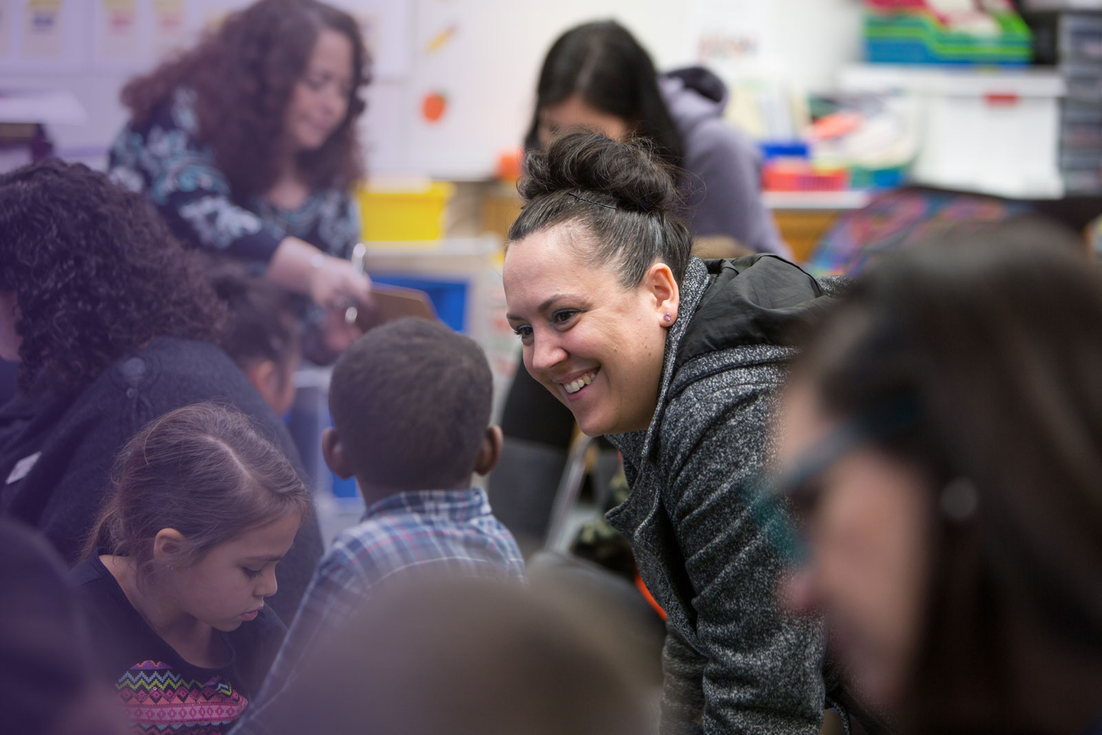 Leading inside the classroom: teacher smiles at student