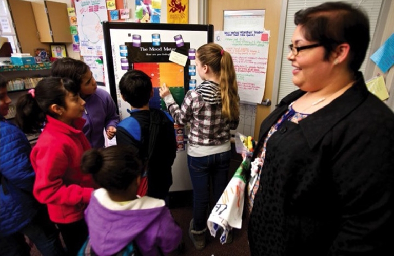 Grade school students and teacher work on social-emotional skills