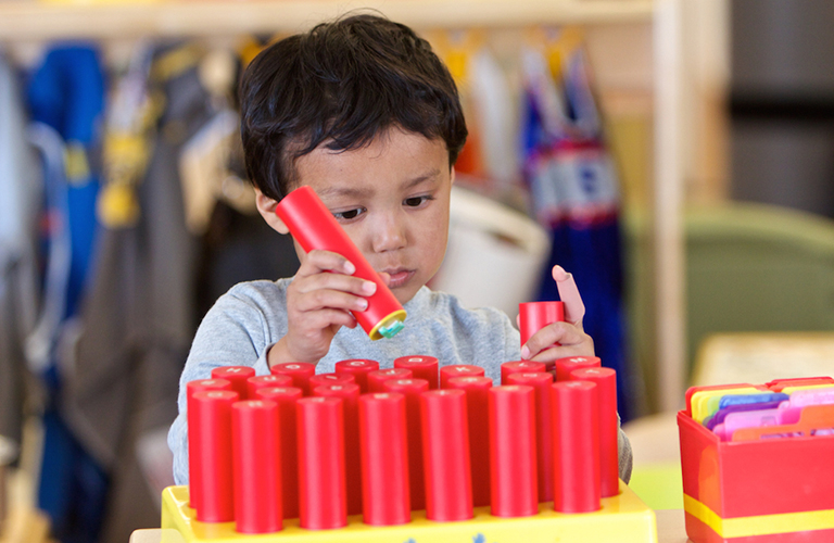 Young boy student plays with stacking pegs