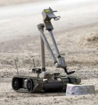 A United States Army explosive ordnance disposal robot pulls the wire of a suspected improvised explosive device in Iraq.