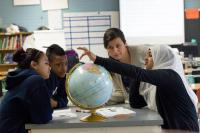 Students talking around a globe